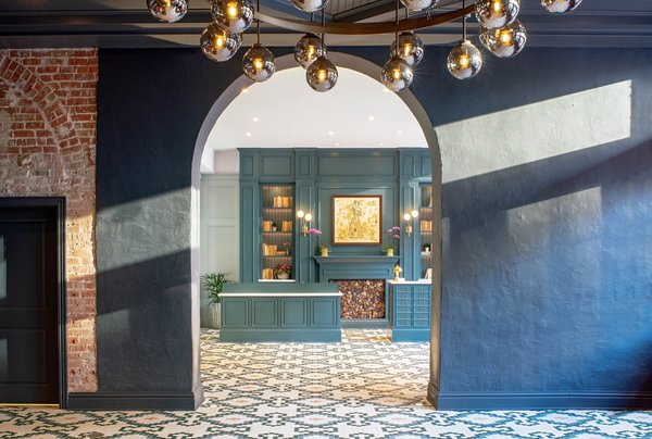 An elegant lobby welcomes guests with evergreen paneled walls and a geometric hex-tiled floor from Daltile.