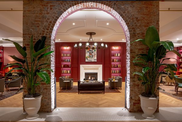 An original brick wall with an arch opening frames views of The Press Room, a cozy lounge lined with paneled walls painted a deep cranberry hue to match the Press Room bar front.