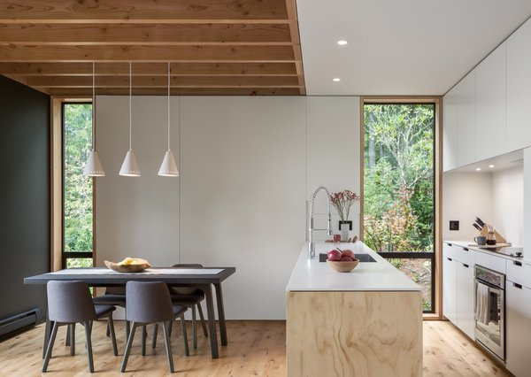 Timber ties the kitchen and dining area to the outdoors, from the exposed wood ceiling joists to Arauco plywood on the island topped with Corian solid surface.