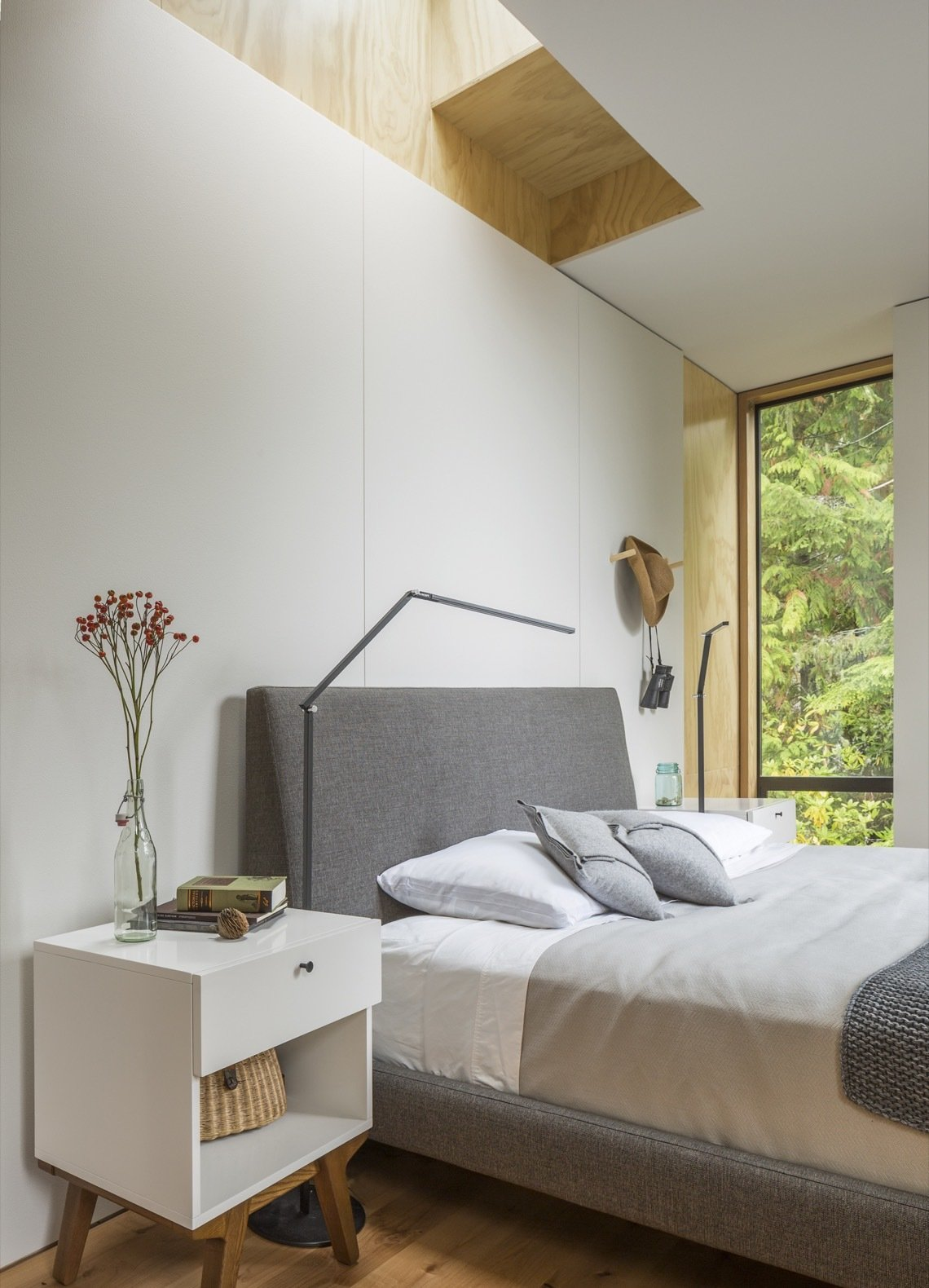 Bedroom, Floor, Bed, Medium Hardwood, and Night Stands The bedroom is illuminated by tall, skinny windows and a skylight that's positioned over the bed for stargazing.    Best Bedroom Medium Hardwood Floor Photos from This Little House in Washington Has Mighty Big Ties to Nature