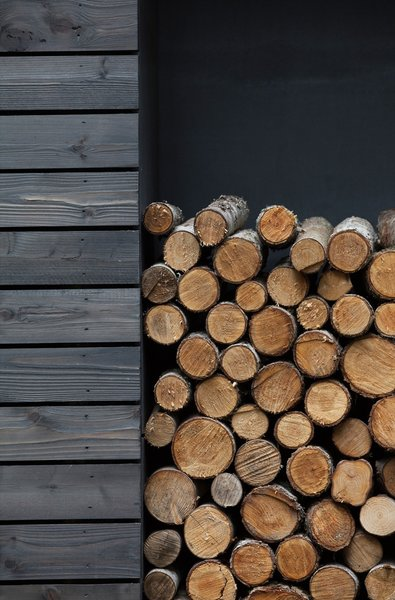 Firewood is neatly stacked in a built-in storage space on the south side of the home.