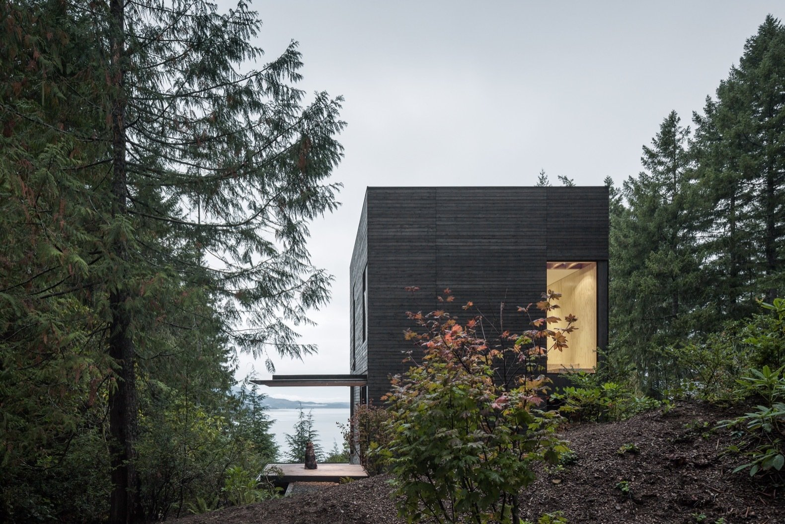 Exterior, Wood Siding Material, Concrete Siding Material, Flat RoofLine, House Building Type, and Cabin Building Type The home is approached from the south with views of Hood Canal below.   Best Photos from This Little House in Washington Has Mighty Big Ties to Nature