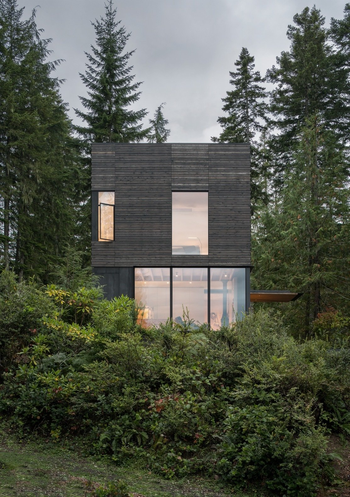 Exterior, Concrete Siding Material, Wood Siding Material, Flat RoofLine, House Building Type, and Cabin Building Type Large windows punctuate the north elevation to pull views of the the water and landscape indoors.   Best Photos from This Little House in Washington Has Mighty Big Ties to Nature