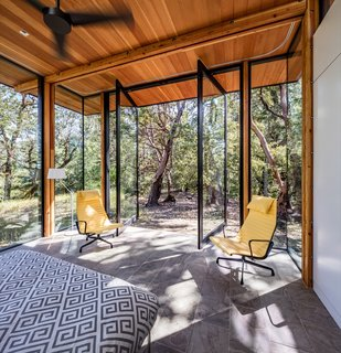 The master bedroom is enclosed in glass, and connects to the outdoors via massive pivot doors.