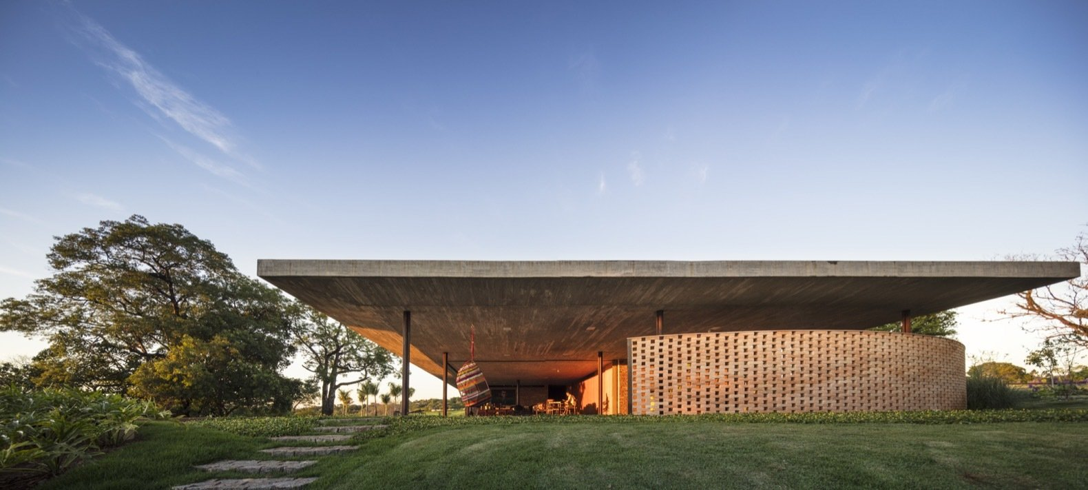 Outdoor, Slope, Grass, Vertical Fences, Wall, Trees, and Walkways The structure is built entirely of reinforced, poured in-situ concrete, except for the metallic pillars on opposite ends of the home.    Best Photos from An Expansive Grass Roof Tops This Modern Brazilian Home