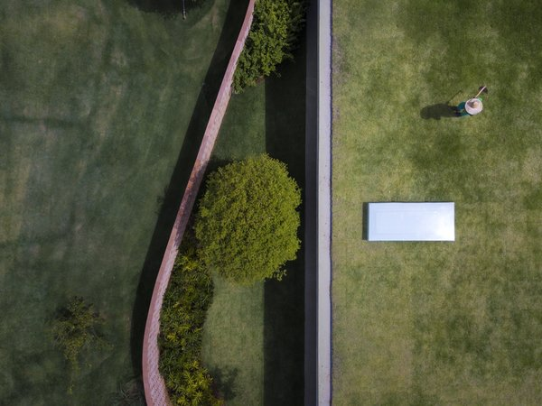 """""""Paradoxically, it defines the different relationships between the internal and external spaces,"""" explains the firm. """"The wall—which is usually a symbol of division and isolation—is, in this project, at times concave and at others convex, embracing the entrance garden and creating transparencies as well as offering protection from the street."""""""