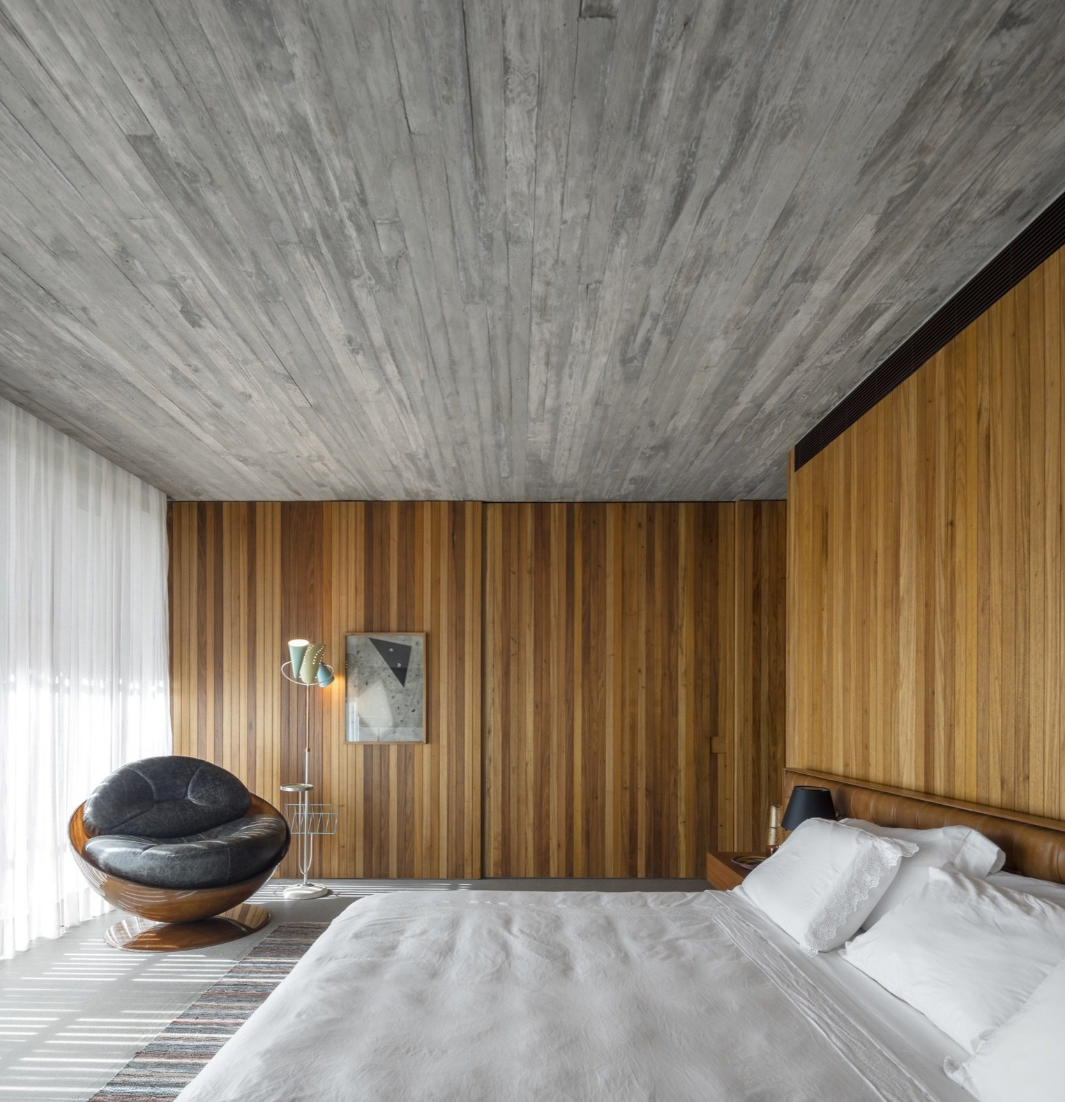 Bedroom, Concrete, Bed, Chair, Floor, Table, and Rug The interiors feature a minimal palette of timber and concrete. The bathroom of this bedroom is hidden behind a sliding wall.   Bedroom Concrete Floor Photos from An Expansive Grass Roof Tops This Modern Brazilian Home