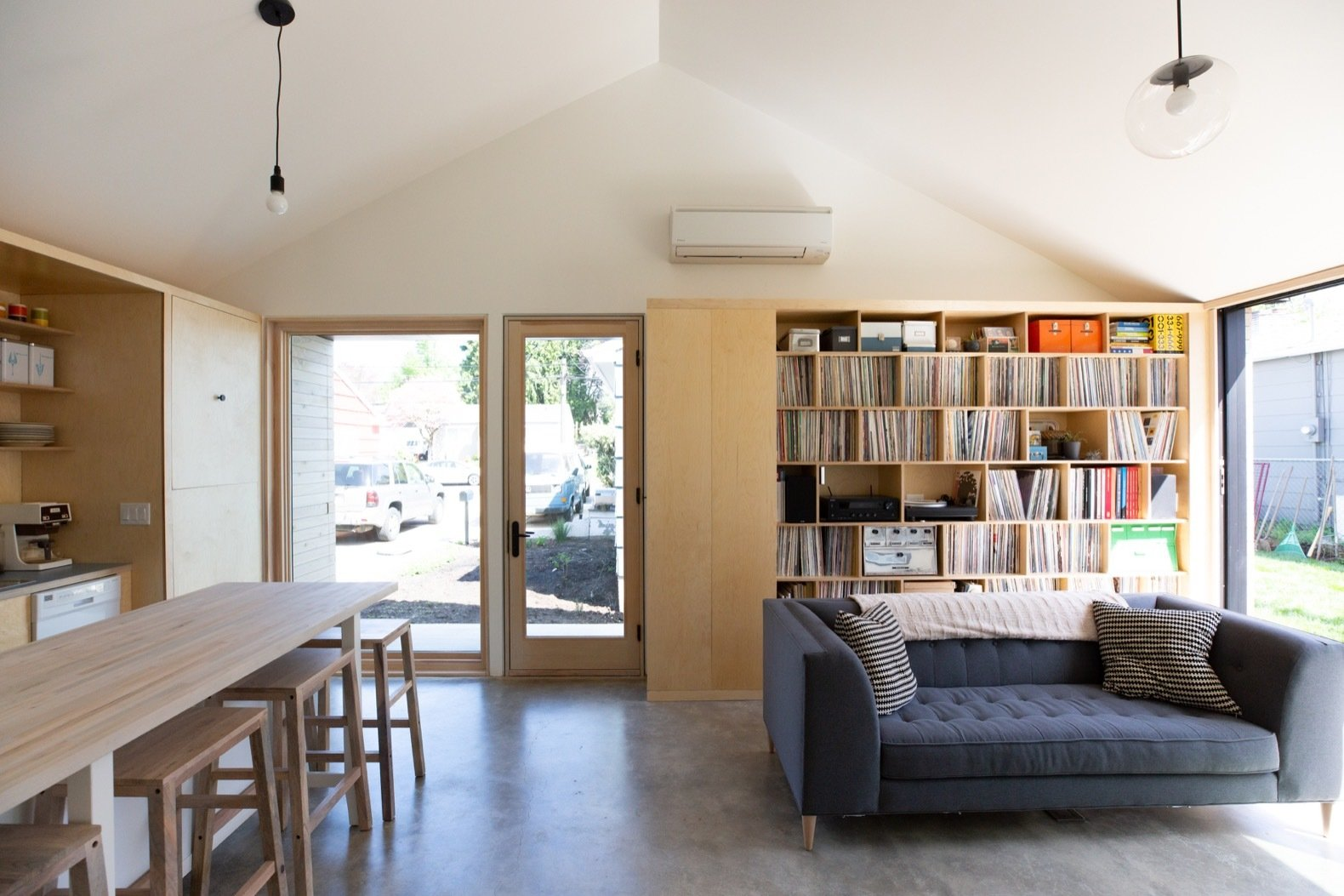 Living, Concrete, Bookcase, Sofa, Storage, Pendant, and Stools A highly efficient ductless mini-split system provides heating and cooling.  Best Living Storage Stools Photos from Budget Breakdown: A Portland Couple Design and Build a Compact Home For $222K