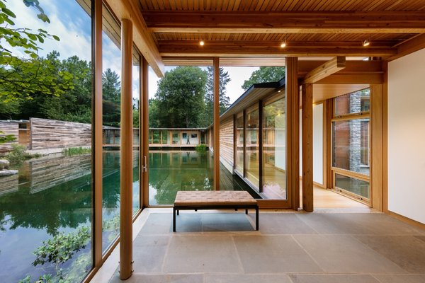 The entry foyer, perched on the pond's west bank, opens to a long glazed walkway elevated above the water that leads to the main living spaces and bedrooms beyond.