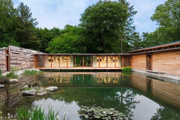 This Striking Net-Zero Home Wraps Around a Serene Pond
