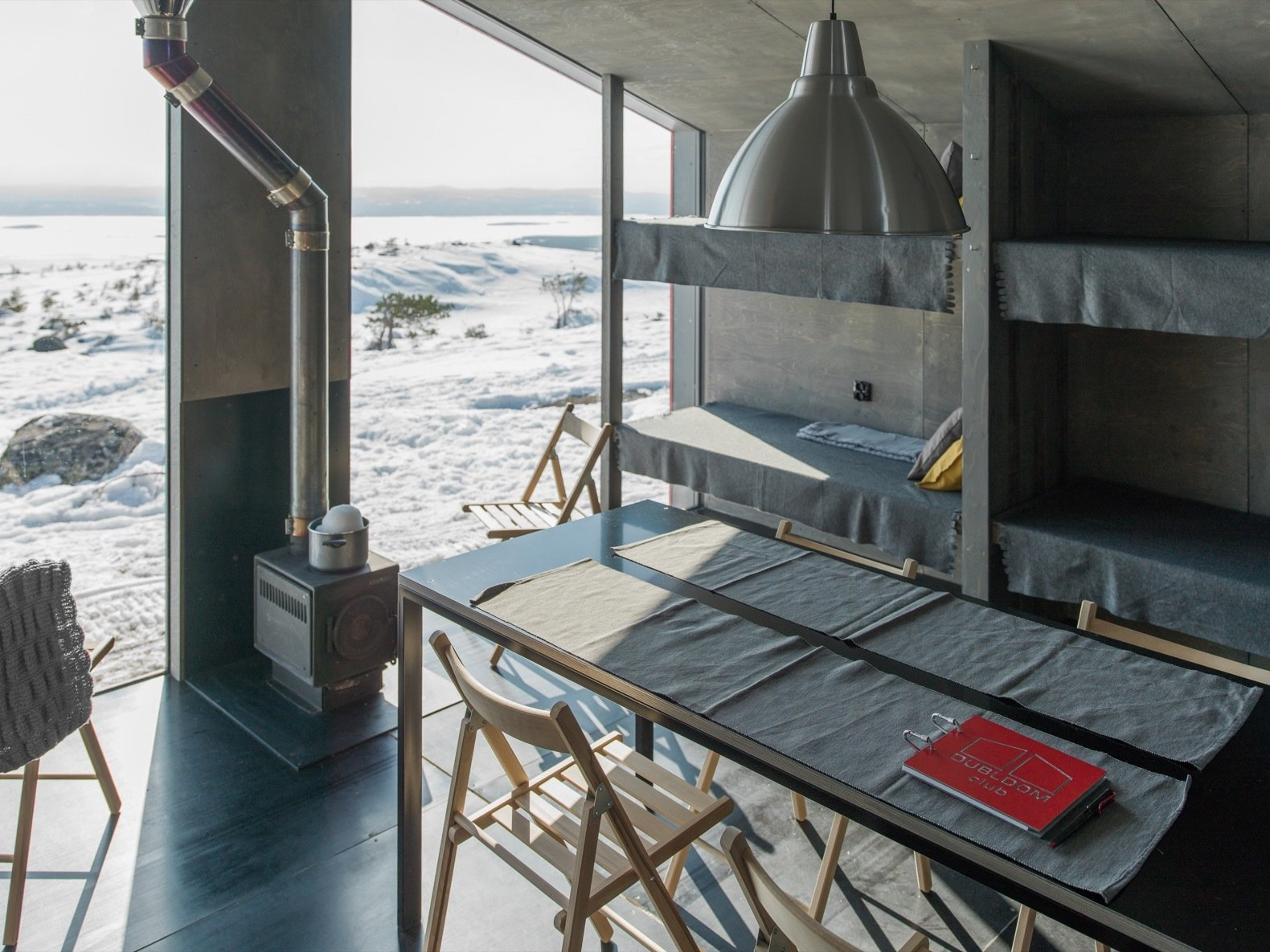 """Living Room, Chair, Table, Wood Burning Fireplace, and Pendant Lighting """"A minimalistic color spectrum was used in order not to distract from the main accent—the view from the window,"""" adds the architects.    Photo 6 of 22 in Go Off-Grid in Russia With This Bright Red Prefab Cabin"""