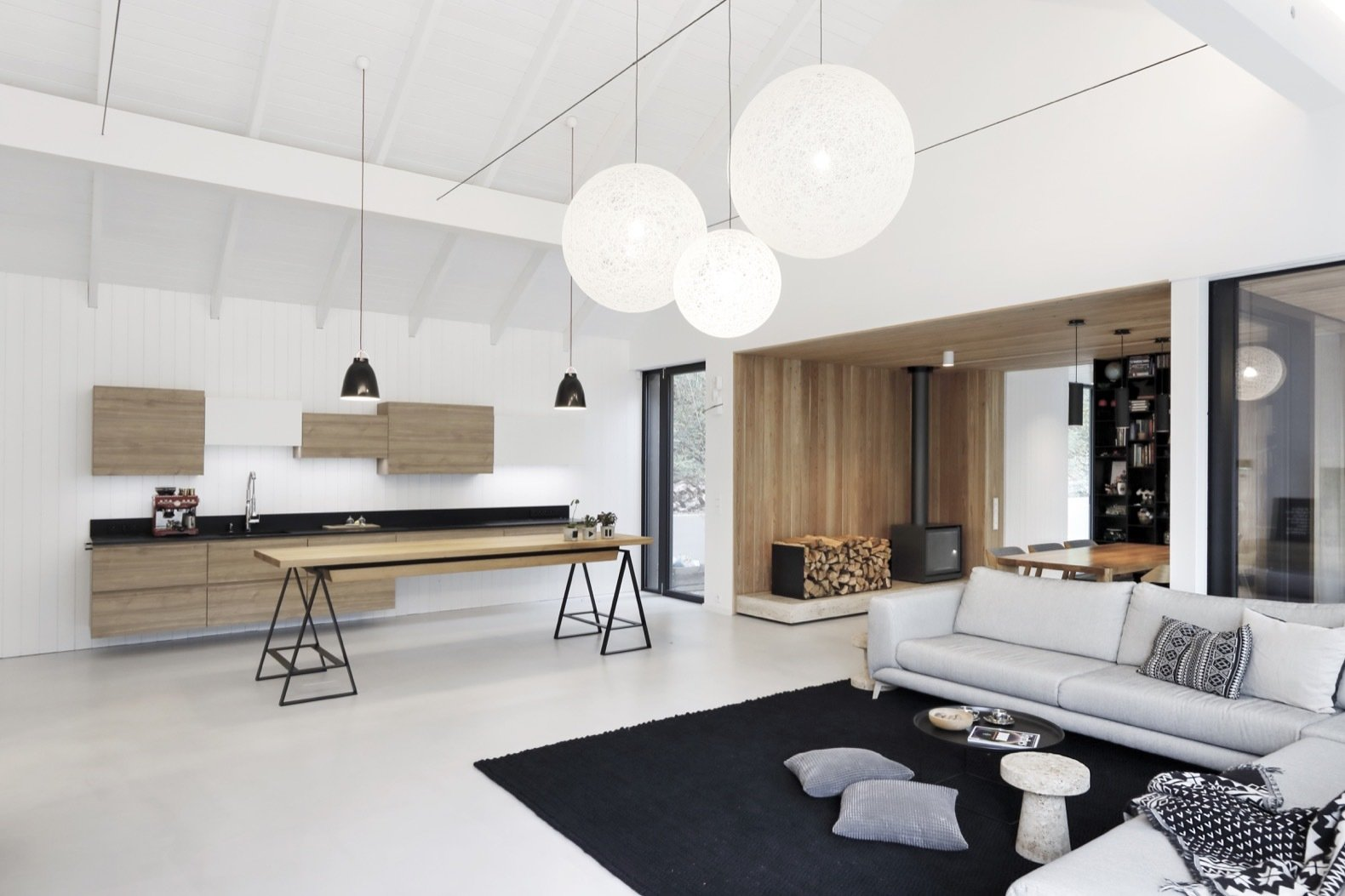 Living Room, Table, Pendant Lighting, Wood Burning Fireplace, Sectional, Coffee Tables, and Rug Floor The vaulted ceiling adds to the home's bright and airy character.     Photo 8 of 15 in This Minimalist Bungalow Will Change Color Over Time