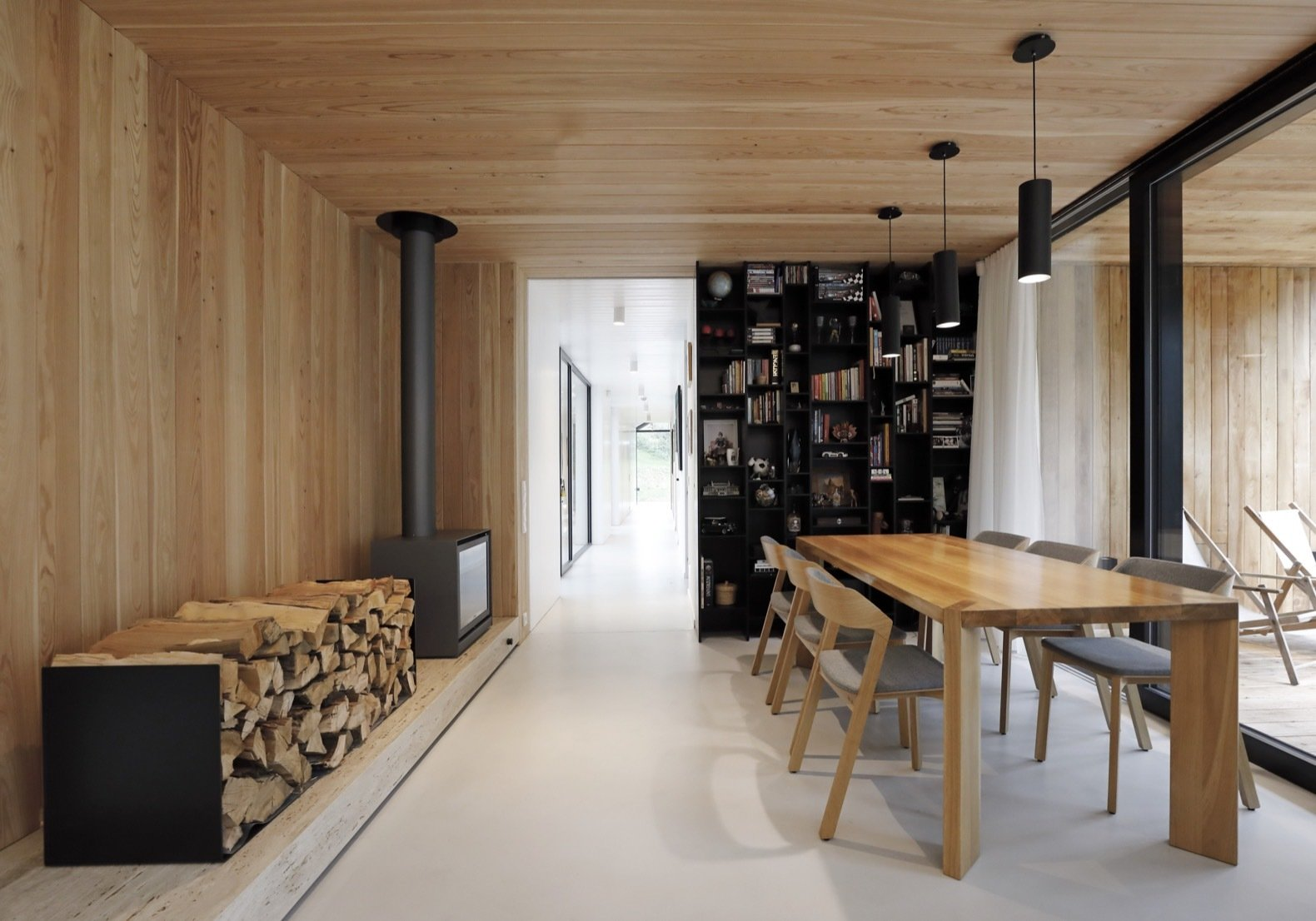 Dining, Shelves, Chair, Pendant, Wood Burning, and Table A wood-burning stove anchors one side of the dining area that connects to the sheltered outdoor terrace.    Dining Chair Shelves Wood Burning Photos from This Minimalist Bungalow Will Change Color Over Time