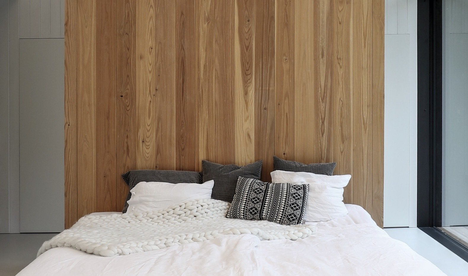 Bedroom and Bed A timber wall imbues warmth into the minimalist bedroom.   Photo 11 of 15 in This Minimalist Bungalow Will Change Color Over Time