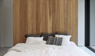 A timber wall imbues warmth into the minimalist bedroom.