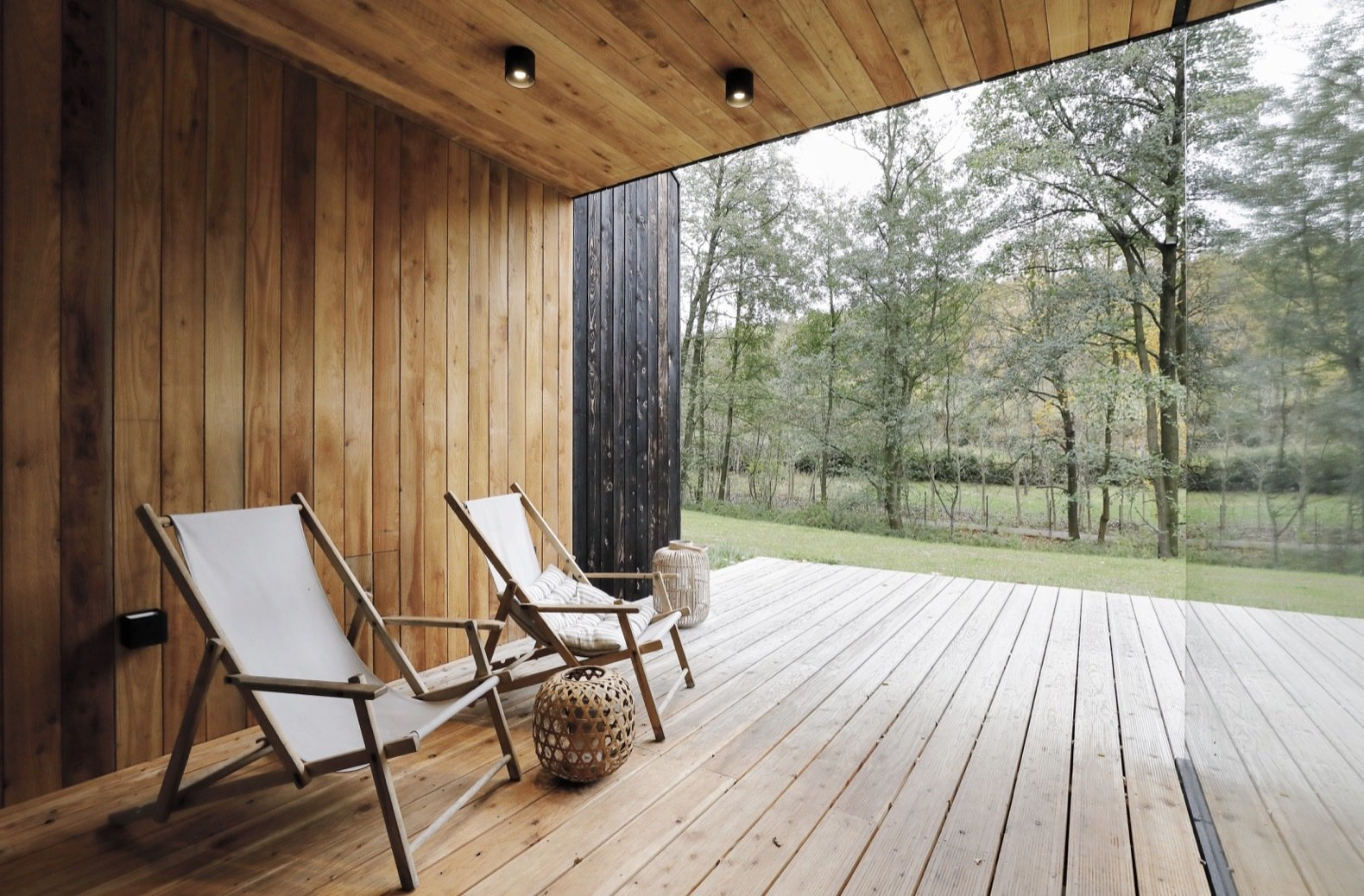 Outdoor, Small Patio, Porch, Deck, Wood Patio, Porch, Deck, Trees, Woodland, and Grass A sheltered outdoor terrace is located near the heart of the home.   Best Photos from This Minimalist Bungalow Will Change Color Over Time
