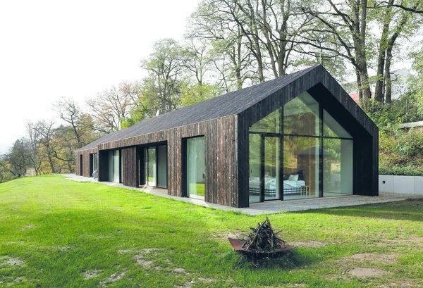 The master bedroom overlooks the landscape through a glazed gable wall, which is shaded with a deep overhang.