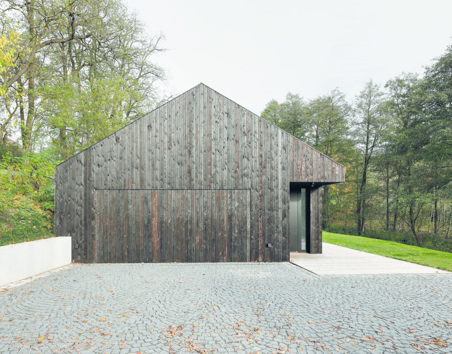 Exterior, Wood Siding Material, Gable RoofLine, and House Building Type The home is accessed from the west, where the garage is hidden behind a charred timber door.    Best Photos from This Minimalist Bungalow Will Change Color Over Time