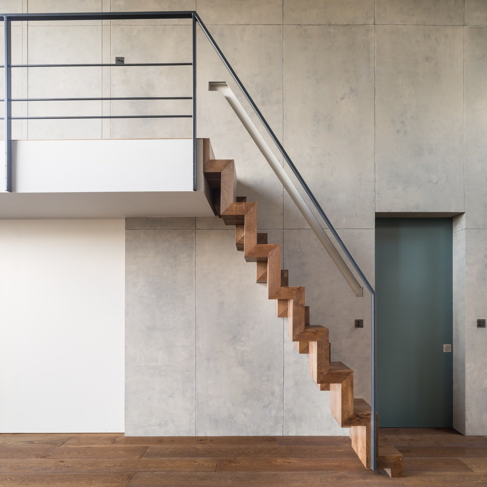 Staircase, Metal Railing, and Wood Tread Sculptural timber-paddle stairs lead up to the mezzanine bedroom.    Best Photos from A Shabby Attic Becomes a Chic, Cathedral-Style Living Space