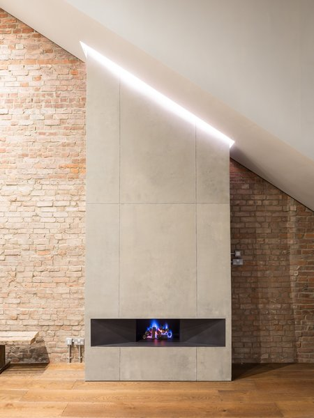 The concrete fireplace draws attention to the sloped ceiling, as well as to the unique lighting feature above.