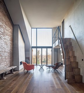 The interior boasts an industrial aesthetic achieved by the exposed brick wall, concrete surfaces, and copper finishes.
