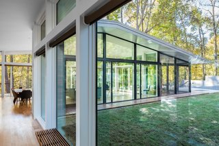 The fully glazed living pavilion embraces views of the forest and pond, and enjoys access to a yard, patio, screened porch, and deck on three sides.