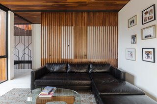 The upper-level family room is furnished with a simple black sectional and a Noguchi table.