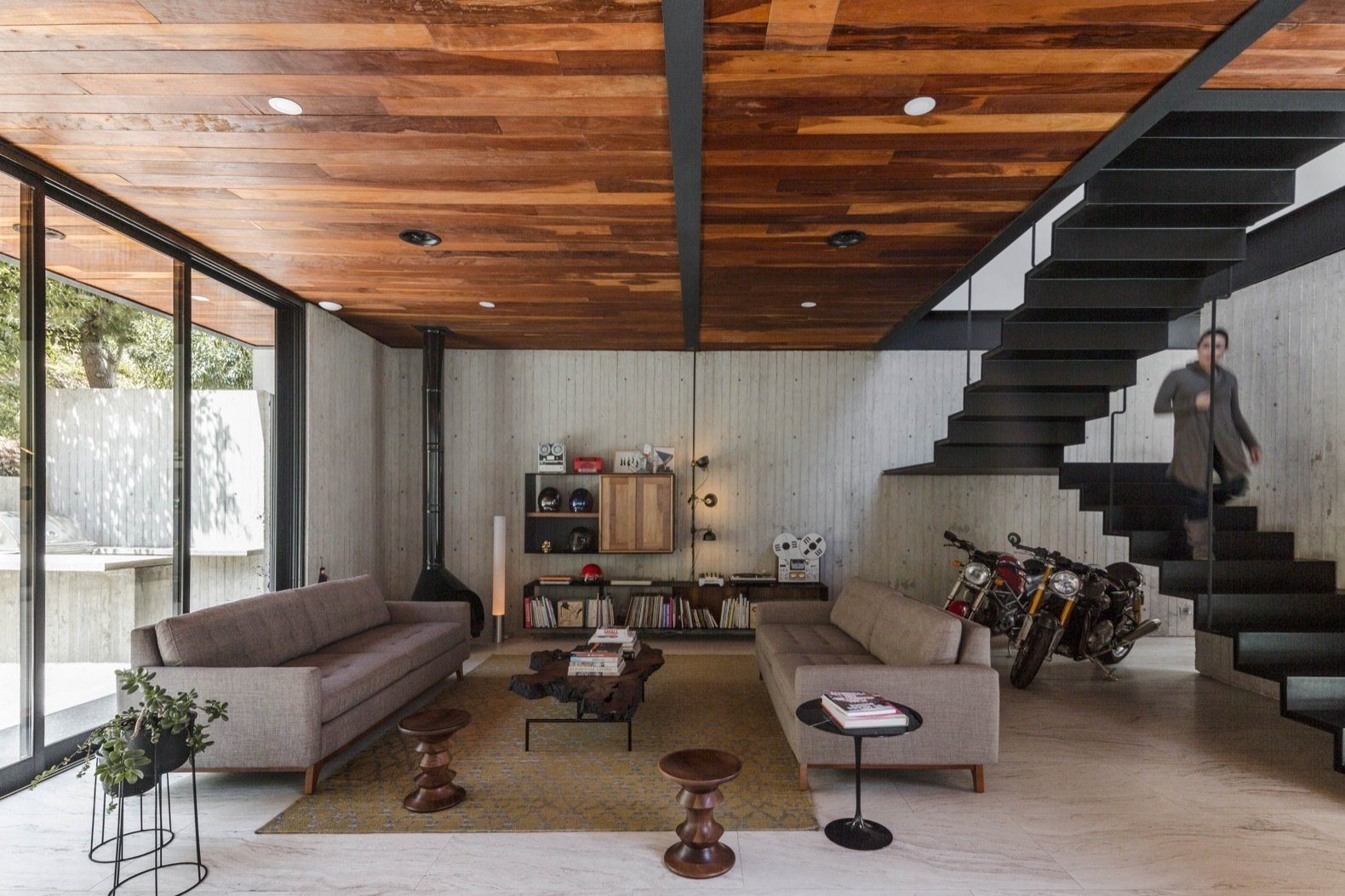 Living, Porcelain Tile, Floor, Bookcase, Recessed, Coffee Tables, Hanging, Sofa, and Lamps A minimalist staircase links the living room to the upper level.    Living Recessed Bookcase Floor Photos from A Modern Mexican Home Rises With Vertical Timber Cladding