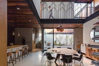Eames molded plywood chairs are arranged around a round midcentury-modern dining table.