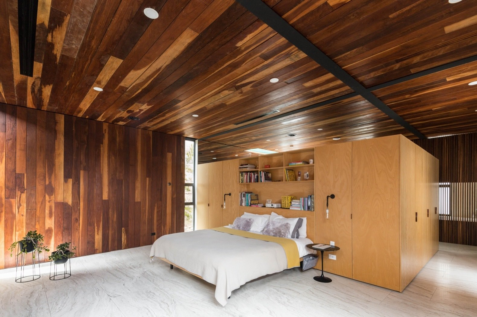 Bedroom, Porcelain Tile, Wall, Bed, Wardrobe, Recessed, Storage, and Night Stands A look at the master bedroom, which unlike the other rooms in the home, features Ipe wood for both the ceiling and walls.    Best Bedroom Wardrobe Bed Porcelain Tile Photos from A Modern Mexican Home Rises With Vertical Timber Cladding