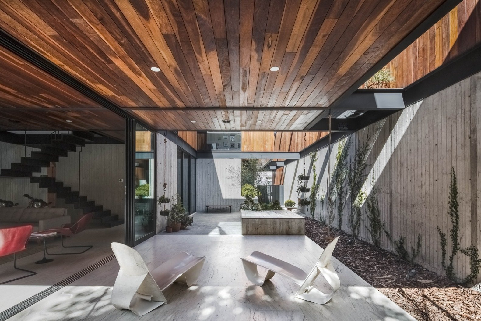 Outdoor, Trees, Gardens, Concrete, Large, Back Yard, Hardscapes, Tile, and Concrete The open voids in the home give the property its beautiful, breezy character.    Best Outdoor Tile Gardens Photos from A Modern Mexican Home Rises With Vertical Timber Cladding