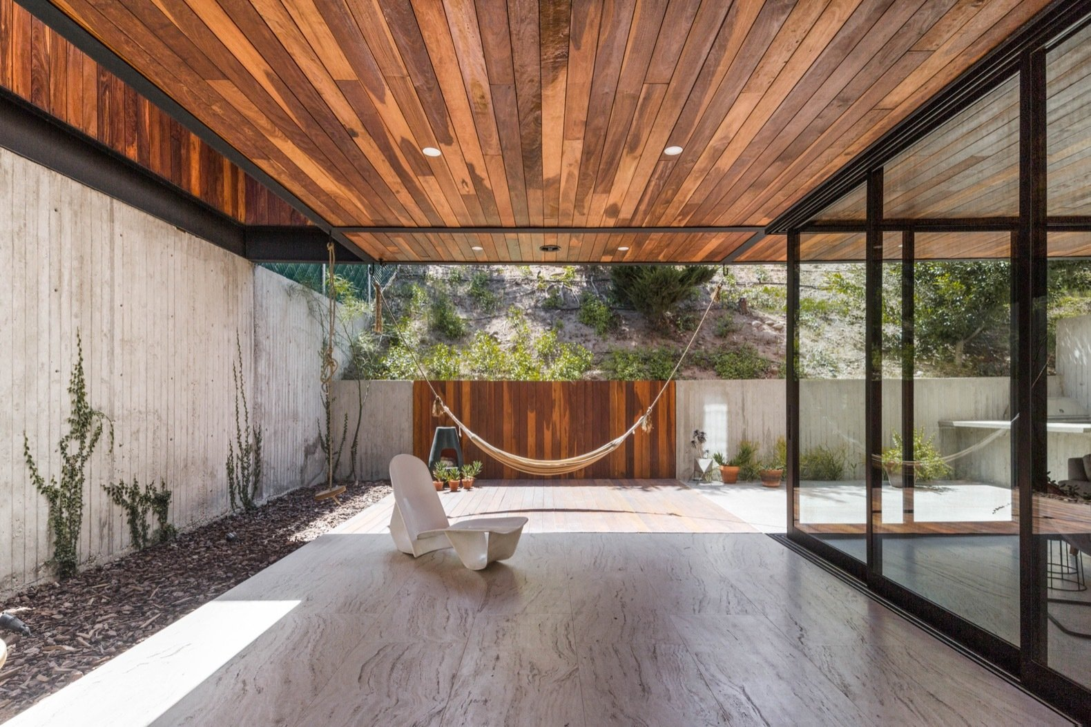 Outdoor, Shrubs, Hardscapes, Back Yard, Tile, Small, Trees, Concrete, and Gardens Protected from prying eyes by a planted slope, the back of the property soaks up the sun with a hammock hung from the ceiling.    Best Outdoor Tile Concrete Photos from A Modern Mexican Home Rises With Vertical Timber Cladding