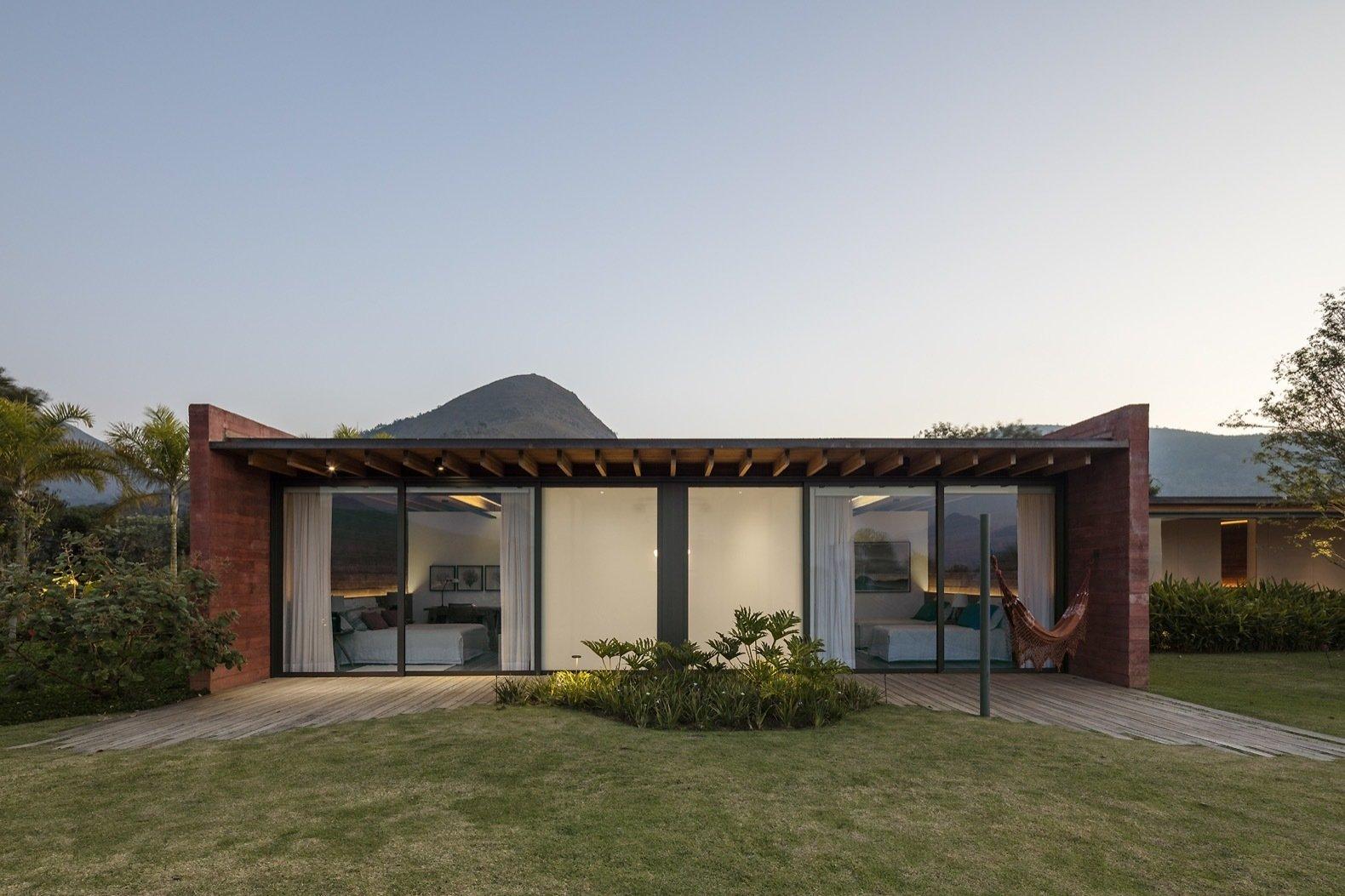 Outdoor, Back Yard, Shrubs, Grass, Trees, and Small Patio, Porch, Deck Sliding glass doors open the bedrooms up to their own private patios; the opaque walls conceal the bathrooms.   Photo 11 of 16 in Pigmented Concrete Walls Tie This Home Into the Landscape