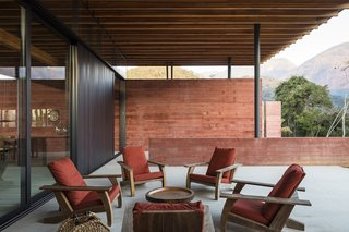 The veranda on the southwest side of the home is shielded from the elements by the roof. The chairs upholstered in red fabric match the pigmented concrete walls.