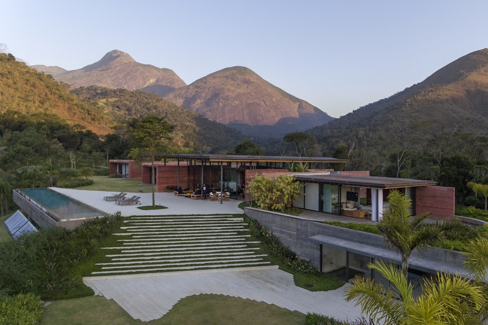 Exterior, Flat RoofLine, Concrete Siding Material, House Building Type, and Glass Siding Material Lush greenery surrounds Casa Terra to make the building feel like an extension of the landscape.   Photo 3 of 16 in Pigmented Concrete Walls Tie This Home Into the Landscape