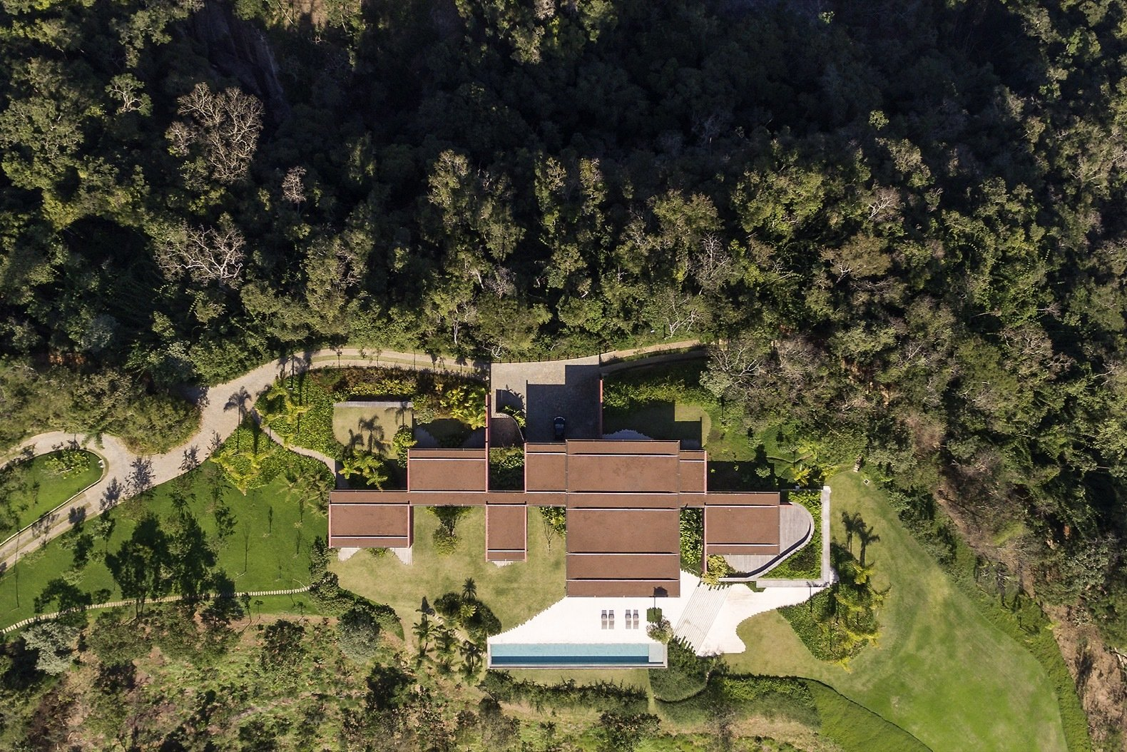 Exterior, House Building Type, Flat RoofLine, Glass Siding Material, and Concrete Siding Material An aerial view of Casa Terra clearly shows how the various rooms branch out from the central circulation axis.  Photo 4 of 16 in Pigmented Concrete Walls Tie This Home Into the Landscape