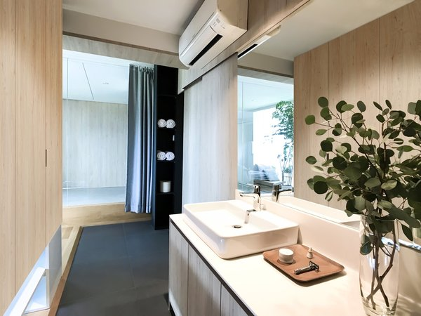 To free up space for a bathtub and separate shower stall in the master bathroom, the vanity and sink have been moved next to the full-height wardrobe that doubles as a divider.
