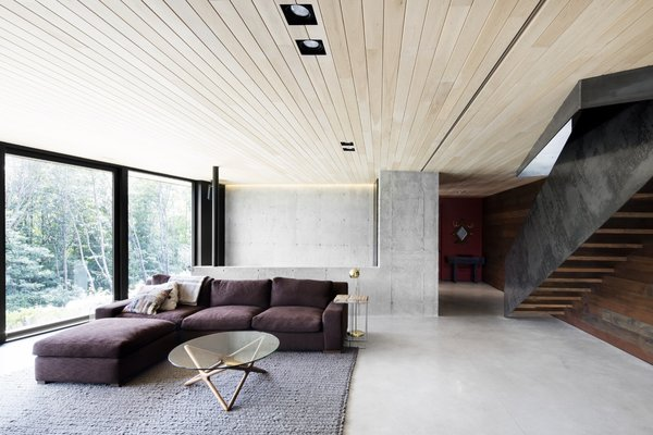 The concrete bearing walls are left exposed in the interior to tie the living spaces with the rock outcroppings.