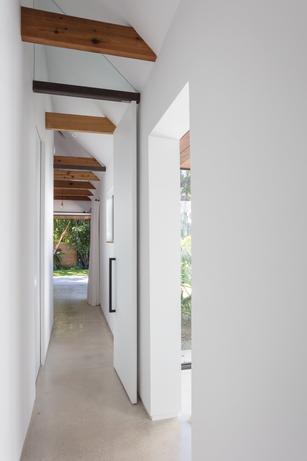 Hallway and Concrete Floor A look down the beamed, light-filled hallway in the new addition.  Photo 15 of 21 in A Minimalist Bungalow in Miami Welcomes a Sleek New Addition