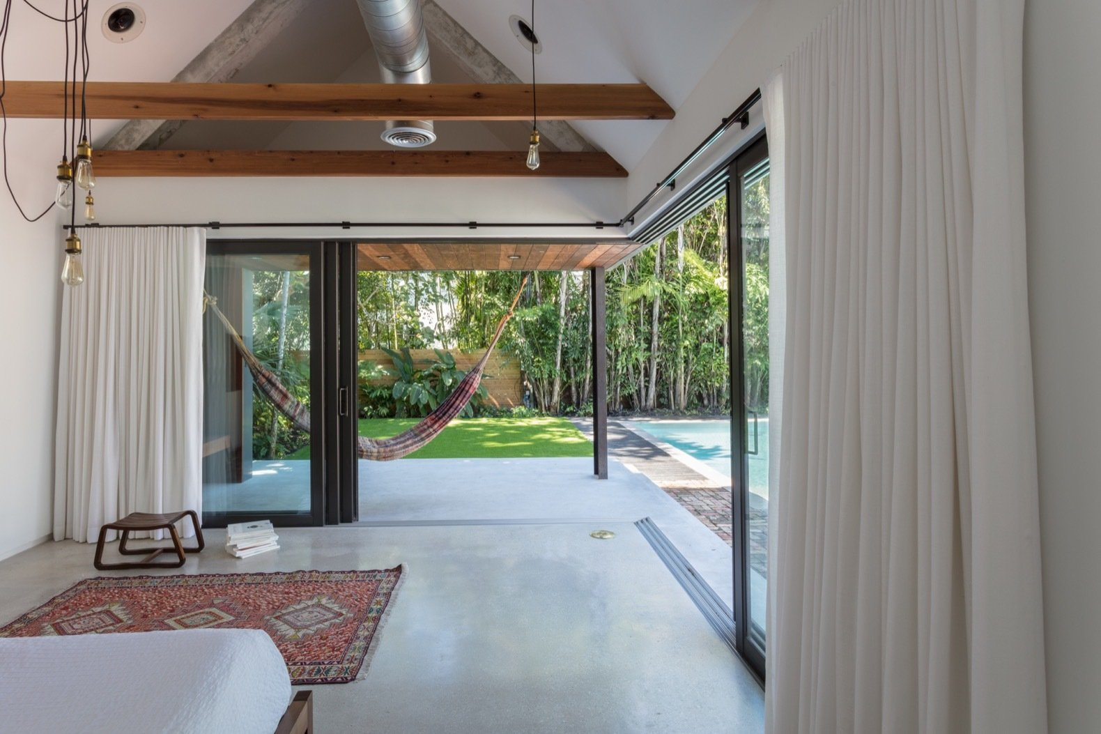 Bedroom, Recessed Lighting, Concrete Floor, Bed, Pendant Lighting, Rug Floor, and Night Stands Sliding glass doors dramatically open the master bedroom up to the outdoors.   Photo 9 of 21 in A Minimalist Bungalow in Miami Welcomes a Sleek New Addition