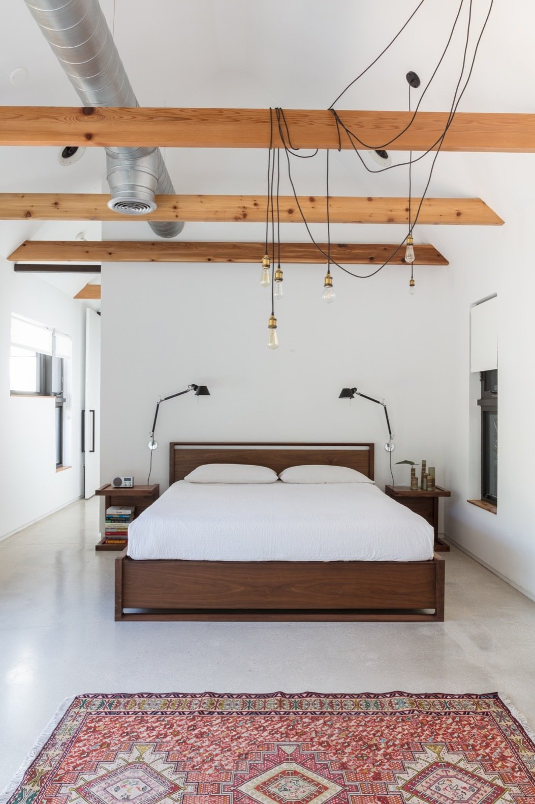 bedroom with wall sconce on each side of bed and 6 center ceiling pendant light bulbs hung with long stringy cords