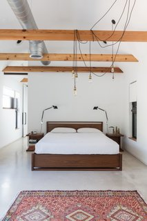 Looking for master bedroom lighting ideas for a vaulted ceiling? Try this one, where a gaggle of Edison bulbs are suspended from a vaulted ceiling and drape over an exposed beam in this otherwise sparse bedroom.