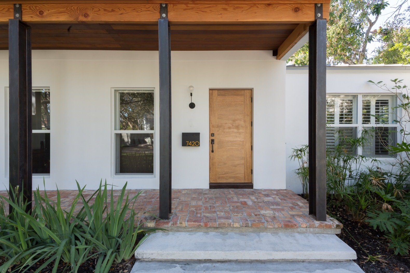 Doors, Exterior, Swing Door Type, and Wood The architects stripped back years of alterations on the one-story bungalow to create a more minimalist and pared-back appearance.    Photo 4 of 21 in A Minimalist Bungalow in Miami Welcomes a Sleek New Addition