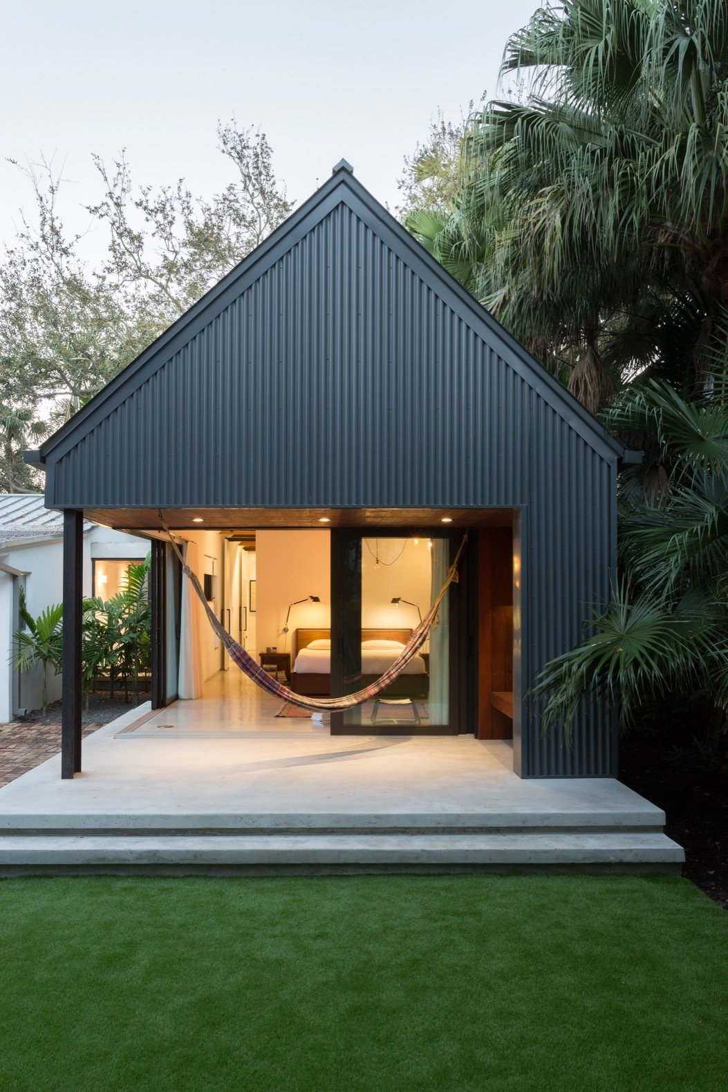 Outdoor, Grass, Trees, Back Yard, Concrete Patio, Porch, Deck, and Hanging Lighting A hammock hangs from the sheltered terrace outside the master bedroom.  Best Photos from A Minimalist Bungalow in Miami Welcomes a Sleek New Addition