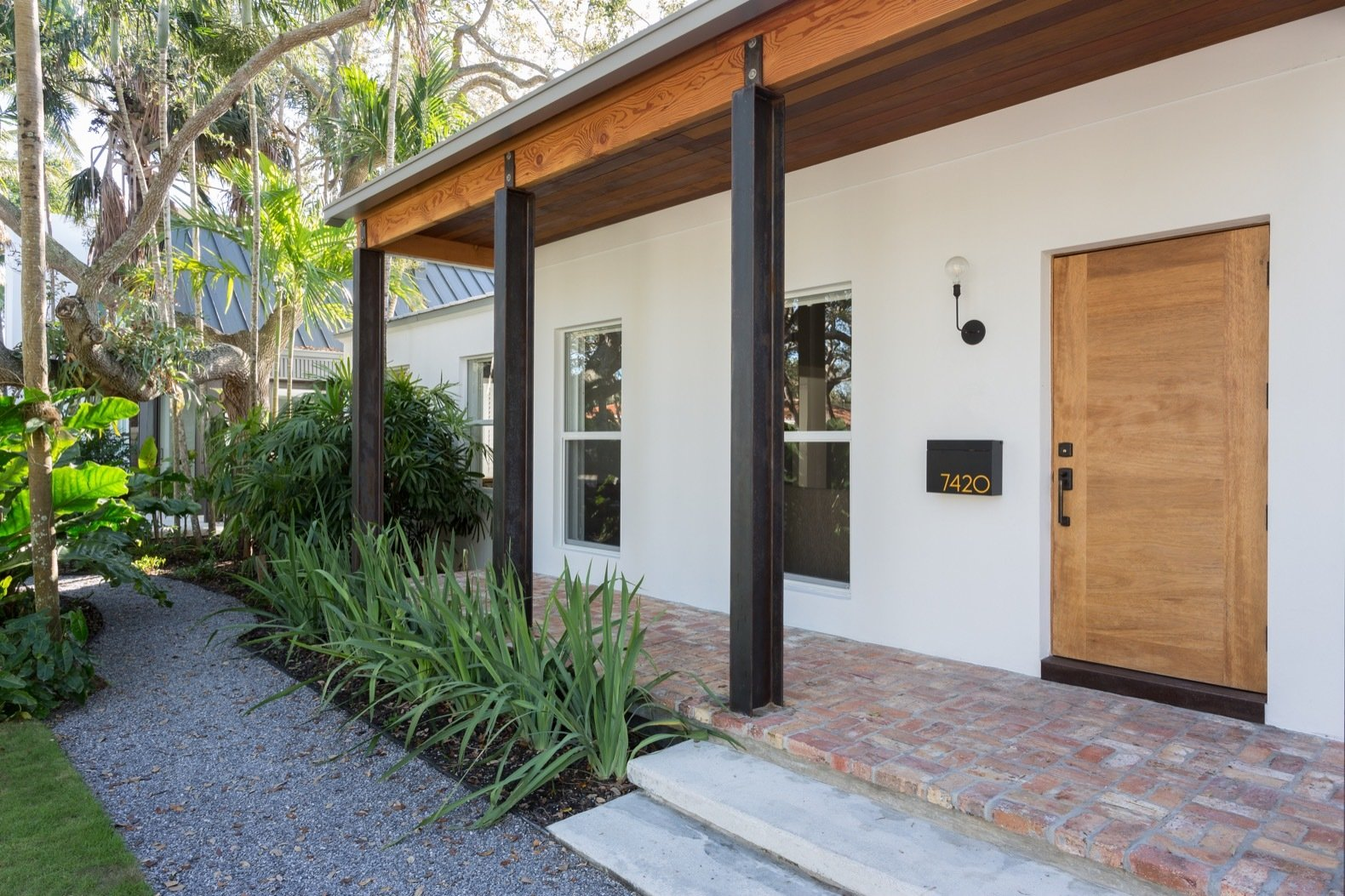 Outdoor, Front Yard, Shrubs, Pavers Patio, Porch, Deck, Trees, Hardscapes, and Hanging Lighting The existing home has been painted a crisp white, while timber elements and brick flooring lend warmth to the space.    Photo 5 of 21 in A Minimalist Bungalow in Miami Welcomes a Sleek New Addition
