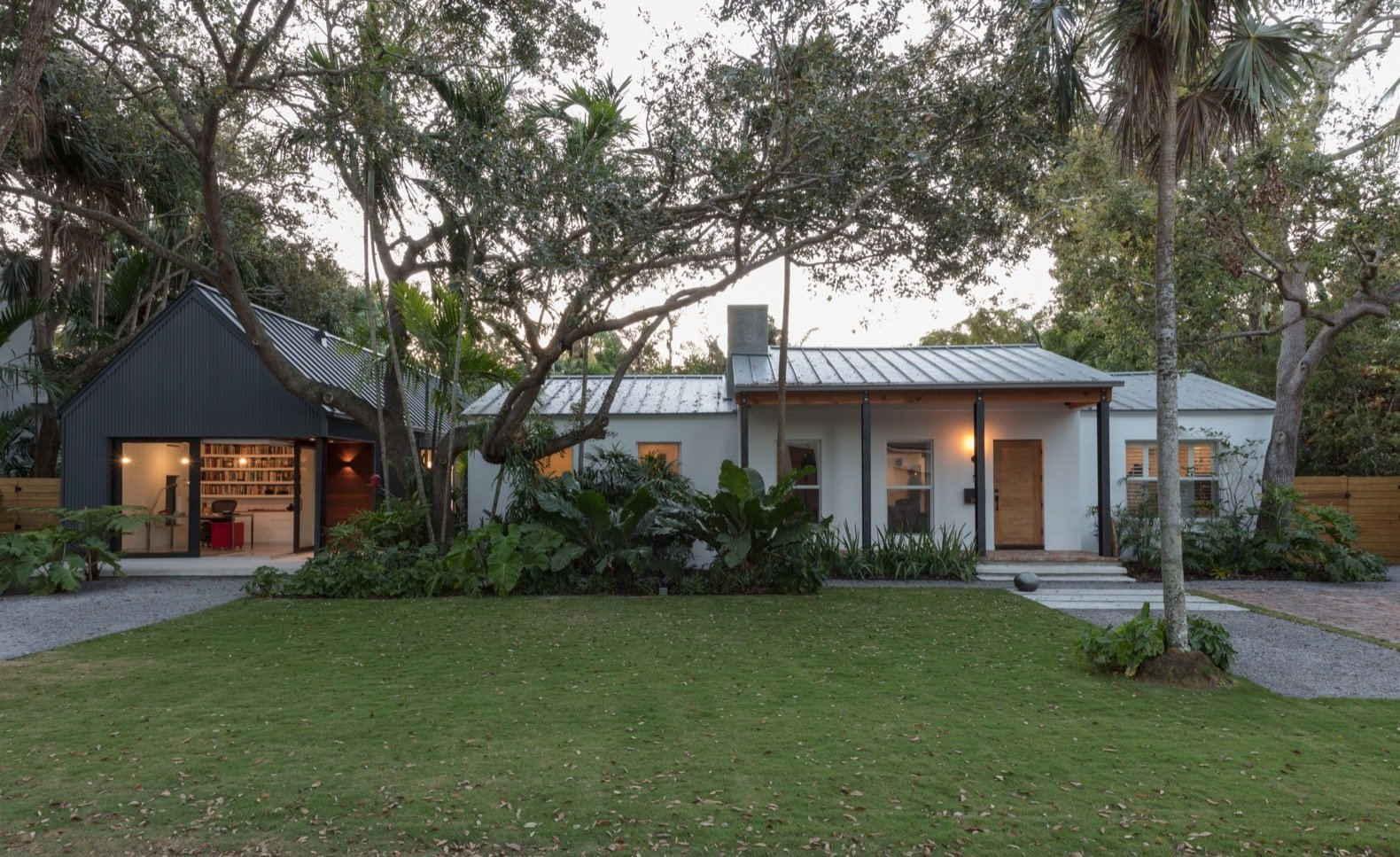 Exterior, Metal Siding Material, Metal Roof Material, House Building Type, and Gable RoofLine The dark and gabled addition offers sharp contrast against the low-lying white-painted bungalow. Elements such as the steel pillars were repeated in both structures for continuity.    Photo 3 of 21 in A Minimalist Bungalow in Miami Welcomes a Sleek New Addition