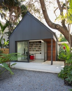 The gabled addition is topped with a standing seam metal roof and is clad in vertical corrugated metal siding.