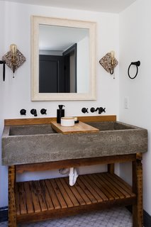 The double vanity in the master bath has a concrete trough sink with a wood slab counter.