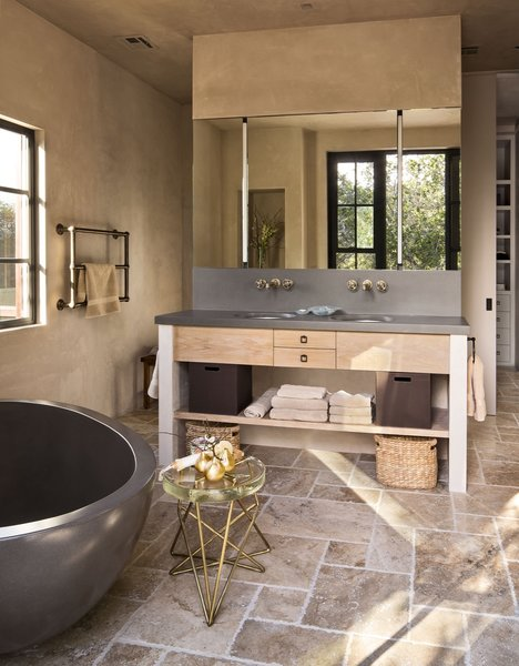 Modern bathroom fixtures are paired with rustic, natural materials.