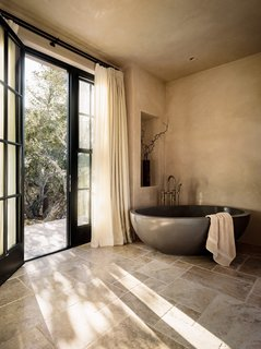 The master bath features a rounded, freestanding bath.